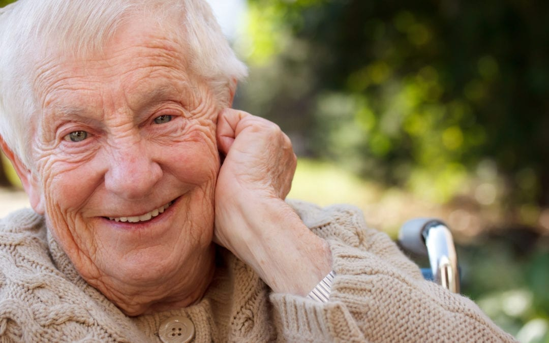 elderly man smiling into camera